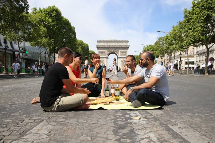 Five person picnic in the middle of famous street of Champs Elysees in Paris