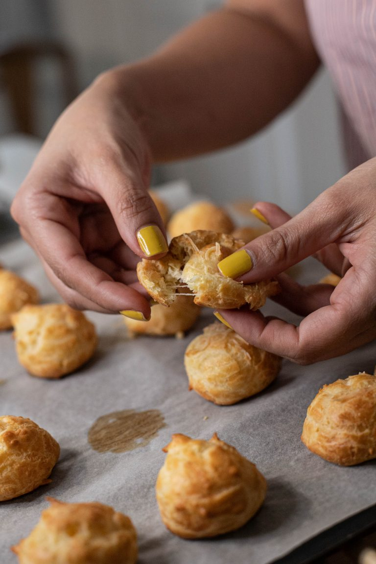 breaking small pieces of salty patee a choux after taking them from oven