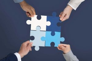 Four hands building a puzzle for effective team building strategies