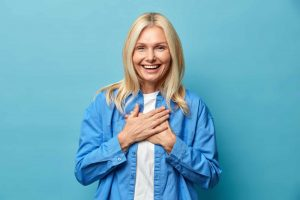 Employee recognition examples that make employees grateful women with hand over heart