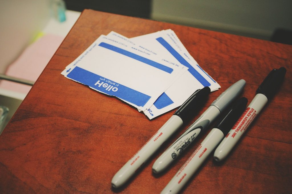 Black markers and a stack of Hello my name is stickers for the Say Your Name backwards 5 Minute Team Building Activity