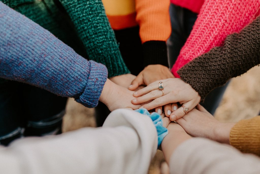 A group huddle between people with their hands in the center