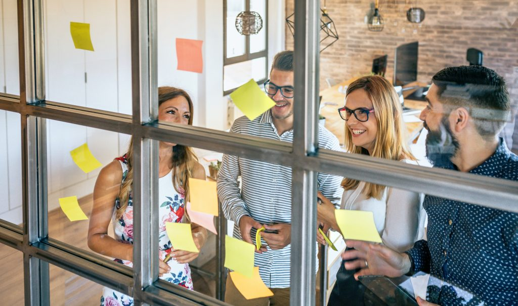 Smiling business workers at a window with sticky notes