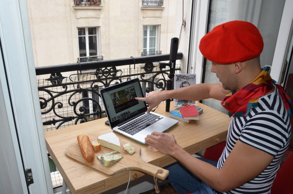 A man wearing a red french beret pointing at a computer screen