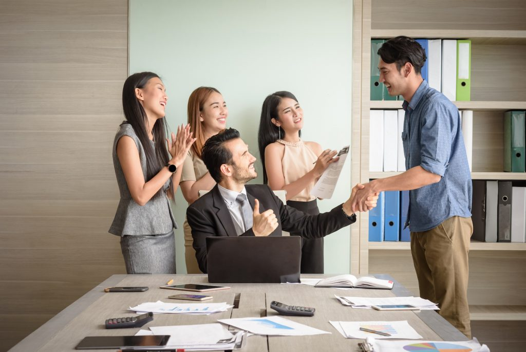 diverse business people clapping and shaking hands in an office environment