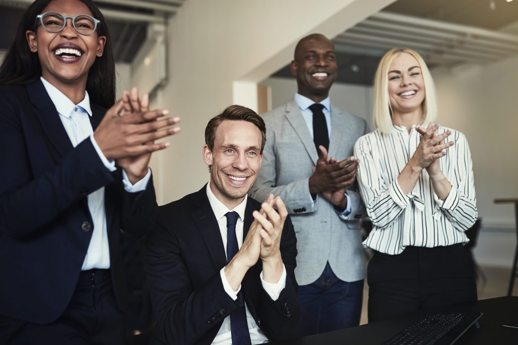 Diverse group of business people clapping standing or sitting around an office table.