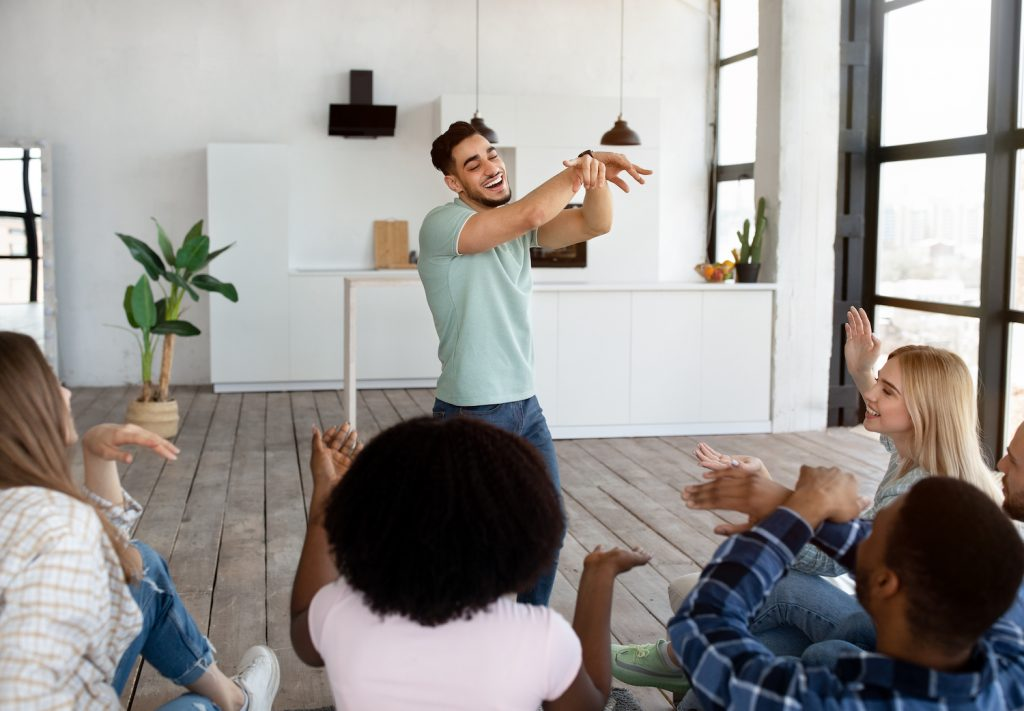 Group of diverse friends playing a game of charades