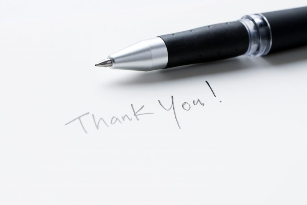 Employee appreciation messages are best when hand written. Ball point pen laying on top of white paper with thank you written on it.