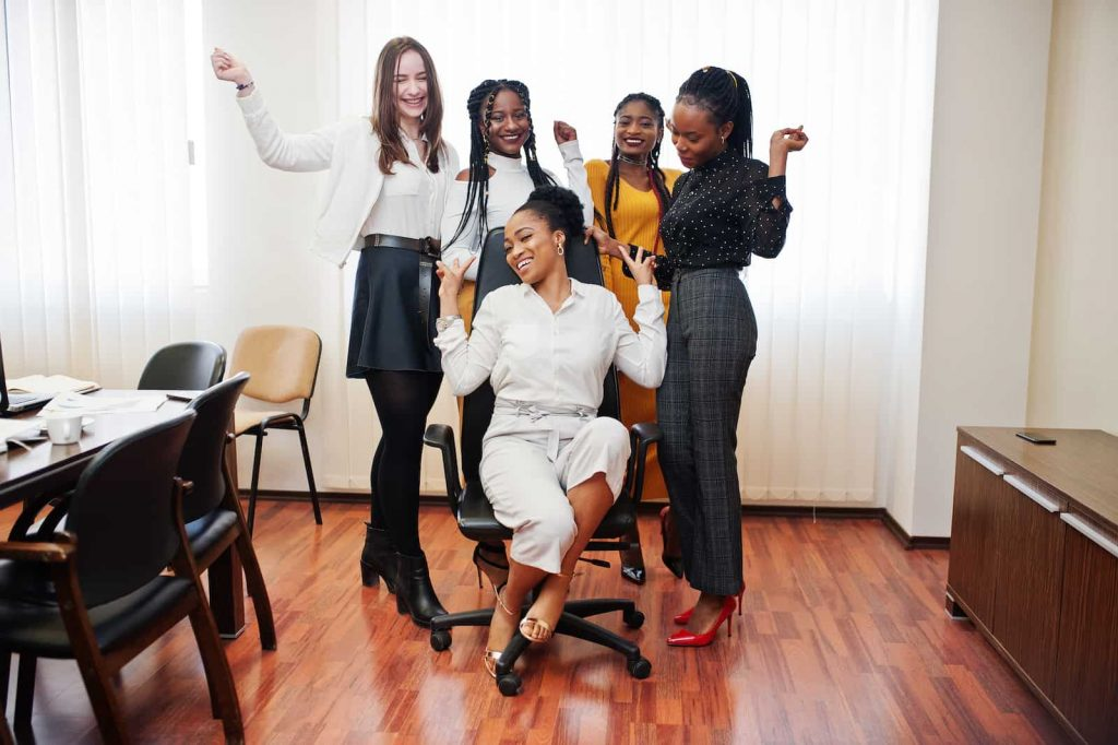 A group of multiracial young women around an office chair
