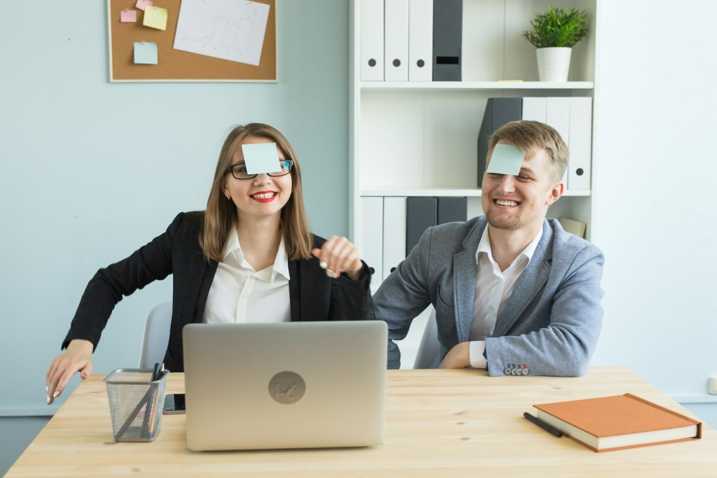 """Colleagues Playing the Icebreaker Game """"Who am I?"""" with sticky notes on their foreheads"""