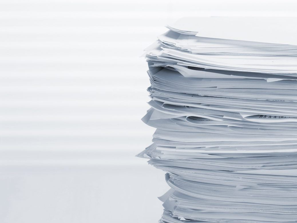Stack of paper documents on office table.