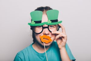 Someone wearing leprechaun glasses and holding fake paper lips to their face