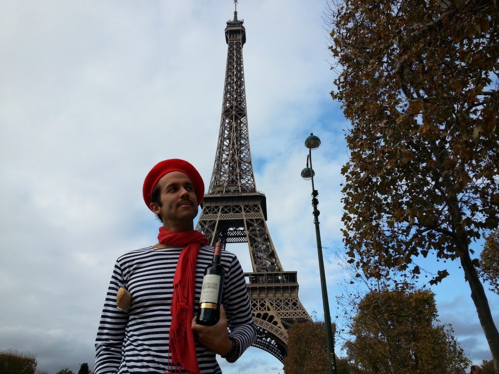 French man standing in front of the Eiffel Tower holding a bottle of wine and baguette wearing a french red beret with matching scarf