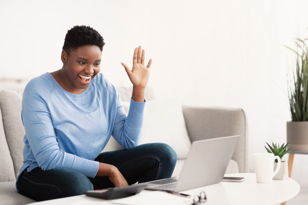 Ice breaker questions for virtual meetings get employees engaged and feeling comfortable on video calls like this employee waving hello to her colleagues online.
