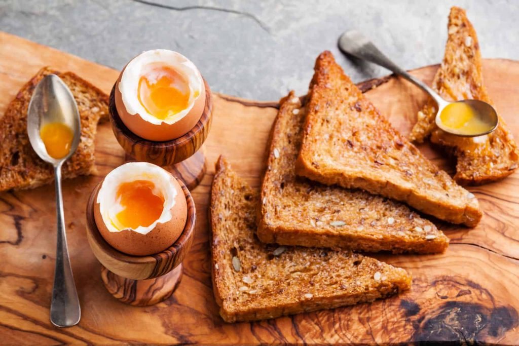 Two soft boiled eggs cracked open with four slices of multigrain toast on a wooden platter