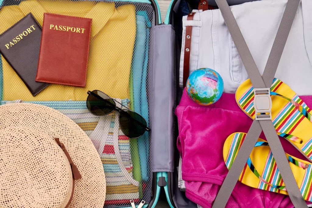 Close up of inside a packed suitcase with passports hat sunglasses sandals on top