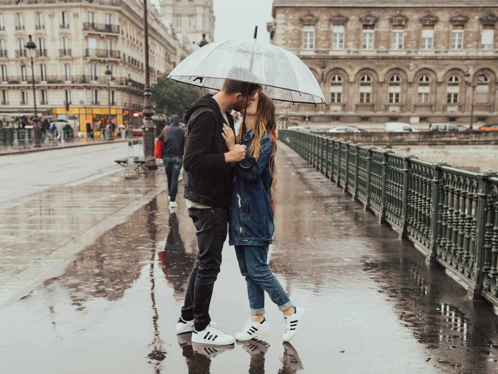 Young couple kissing in the rain while standing on a bridge in Paris under a clear umbrella an essential item on a packing list for Paris
