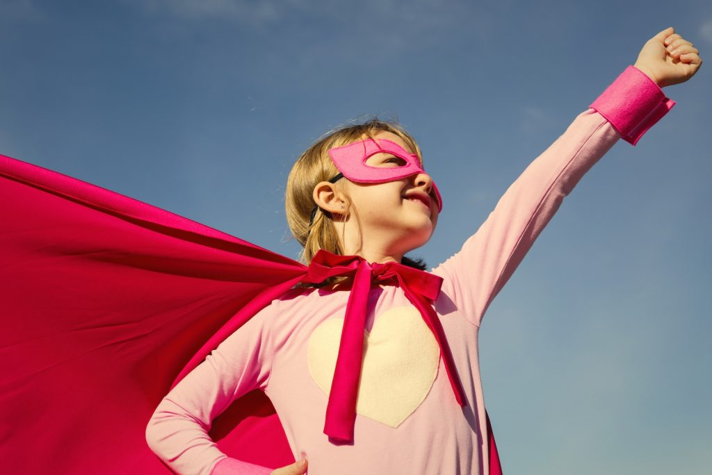 The best first date question - what would your super power be? Little girl dressed in pink with a red cape and mask pretending to be a super hero.