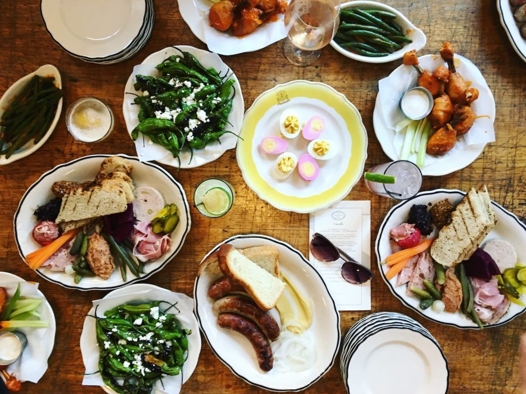 Wooden table full of different foods like sausages, chicken wings, devilled eggs.