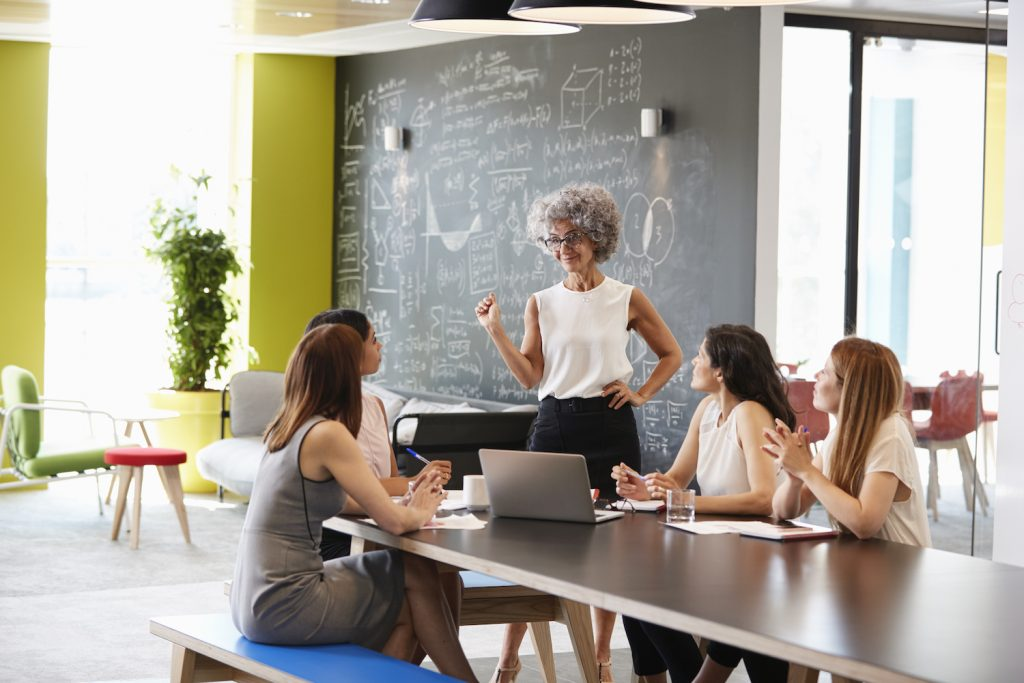 A female boss presenting at a meeting with four employees sitting at a board room table near her.