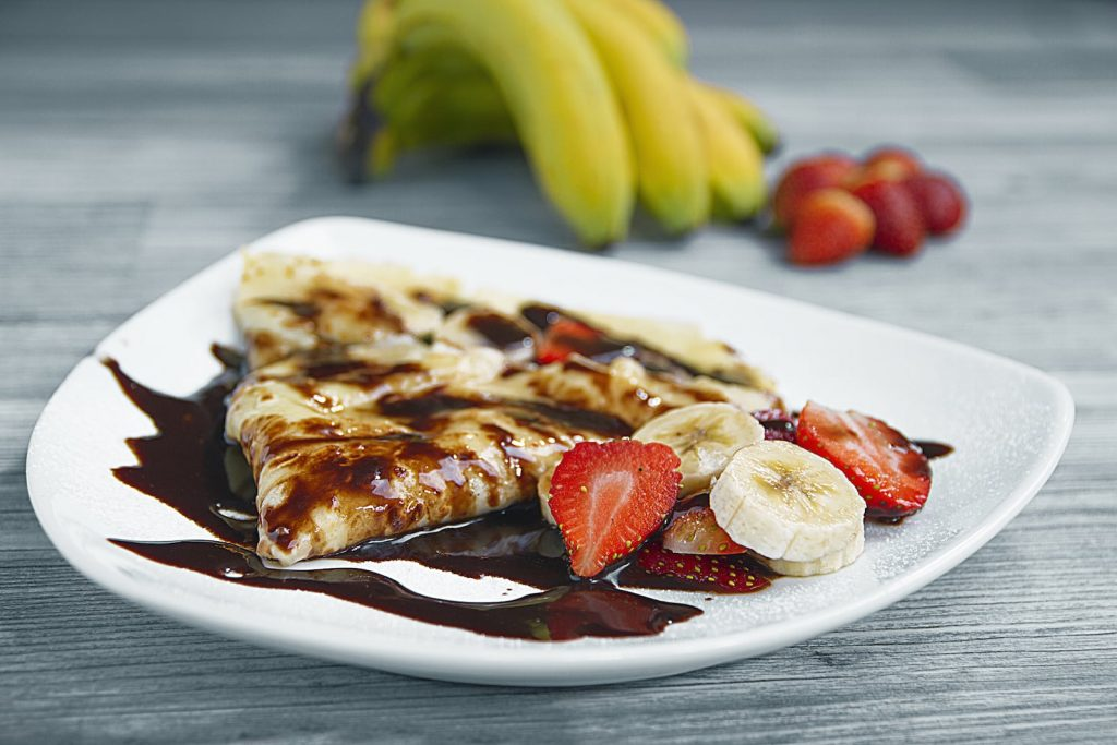 a plate a crepes on a white plate with bananas, strawberries and drizzled with chocolate sauce.