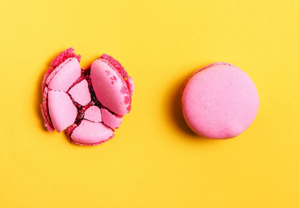 Two french pink macarons one smashed the other not side by side