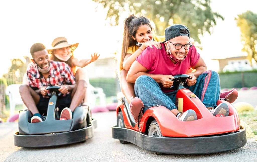 Two young diverse couples riding separate go karts.