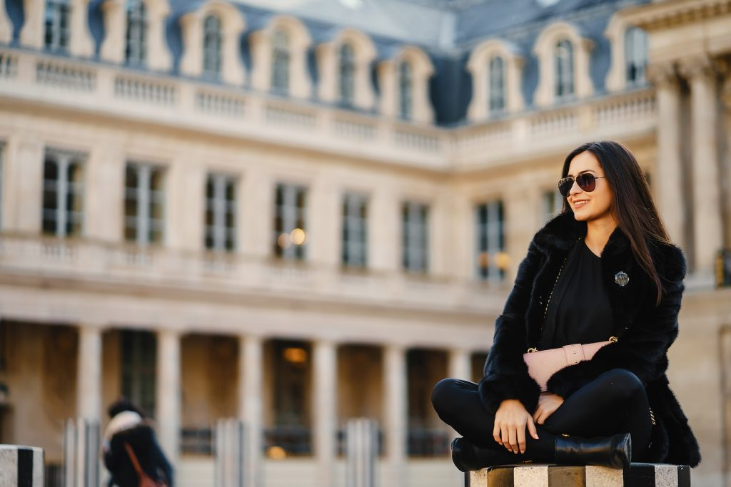 Young fashionable women sitting outside a Paris landmark all dressed in black with sunglasses on holding a blush pink clutch