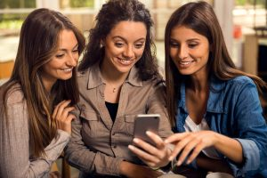 Three young women looking at a phone