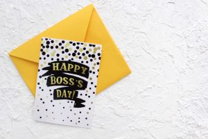 A happy bosses day 2021 greeting card with a yellow envelop on a white table