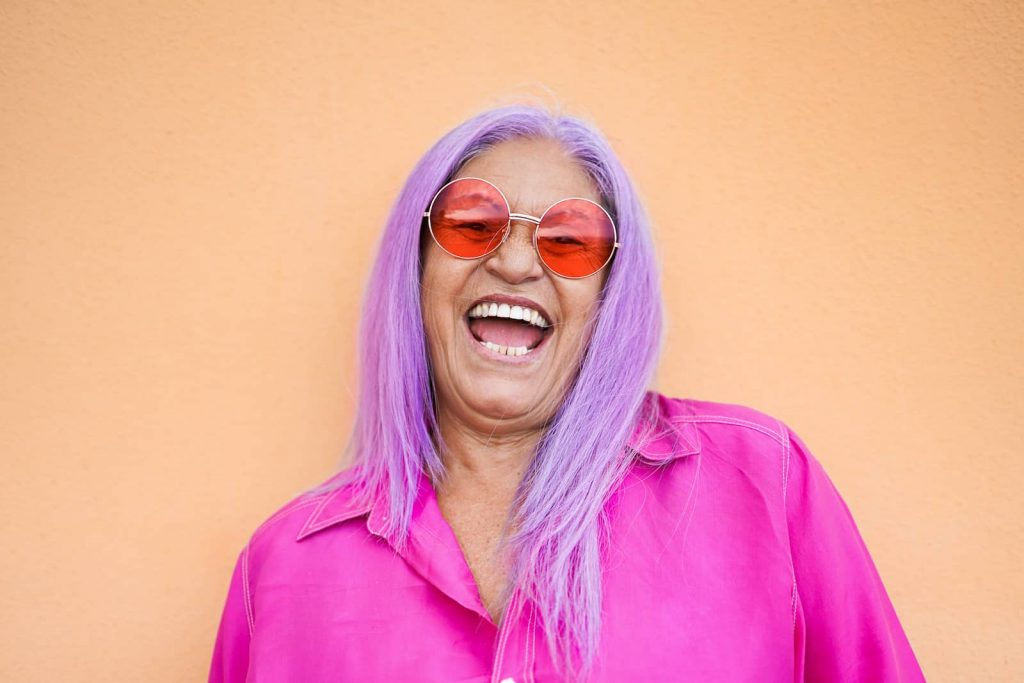 Women with Purple hair red round sunglasses and a super vibrant pink neon shirt all ready for wacky hair day, one of many great virtual spirit week ideas.