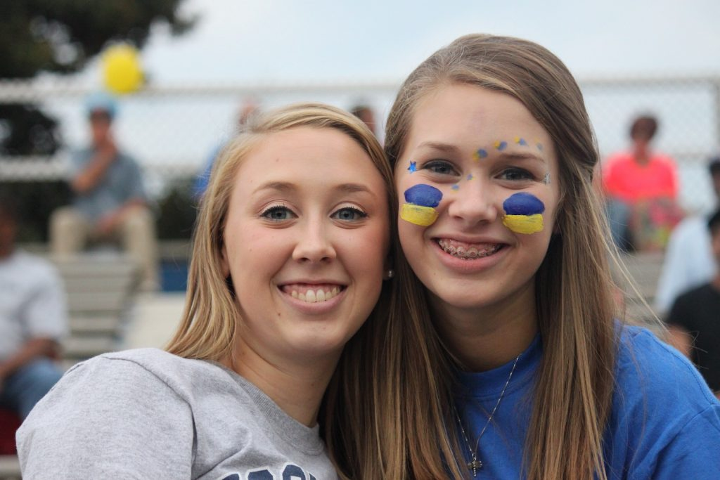 Two teenagers both smiling, one with her face painted in school colors at a high school event both.