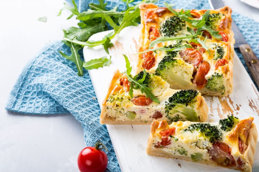 slices of homemade vegetarian quiche on a white wood platter with leaves of arugula sprinkled on top