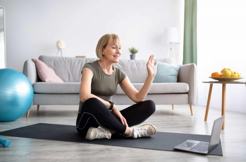 Mature women sitting crossed legged on a yoga mat waving at her online instructor
