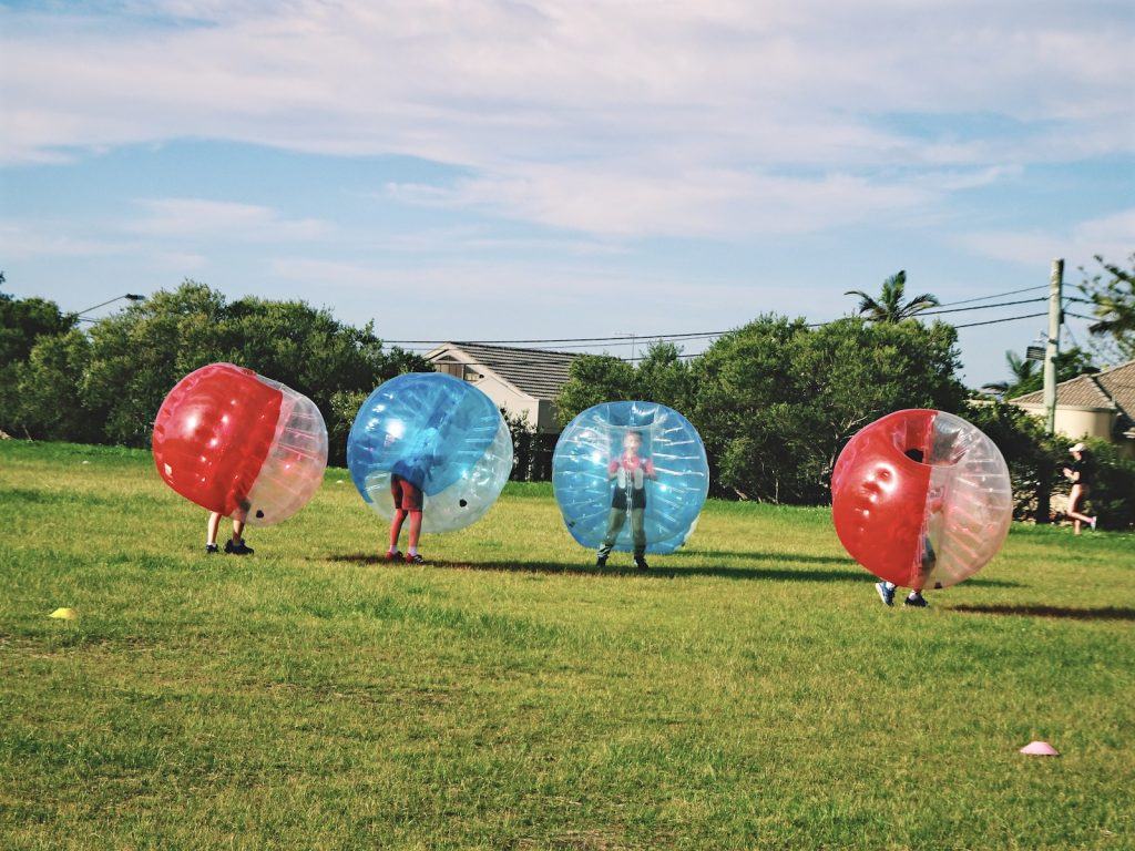 Group playing bubble soccer on green grass