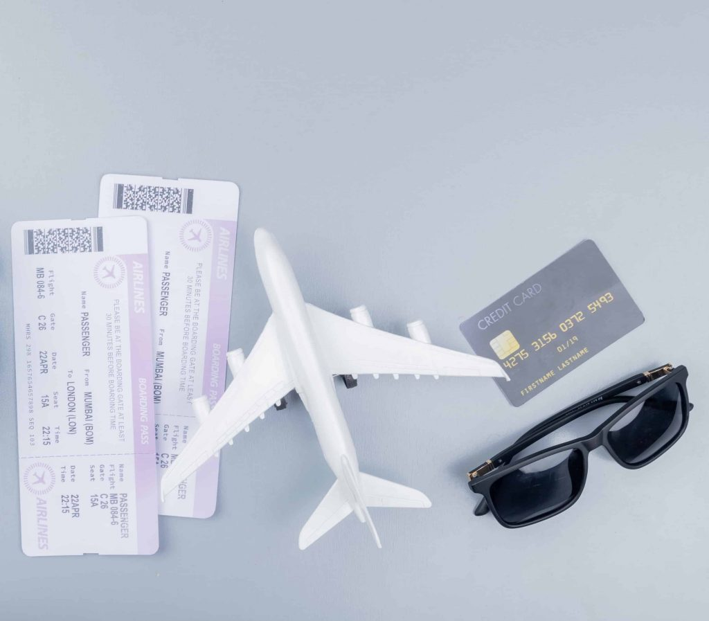 Two paper plane tickets toy model airplane sunglasses and a credit card on a grey background