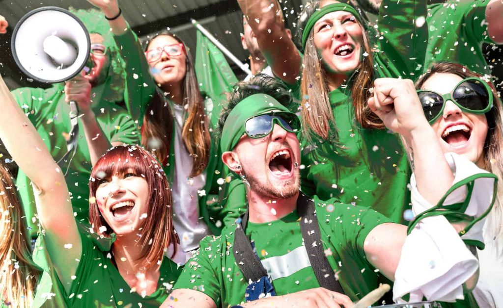 Happy sports fans all dressed in green cheering on their team with confetti and megaphones.