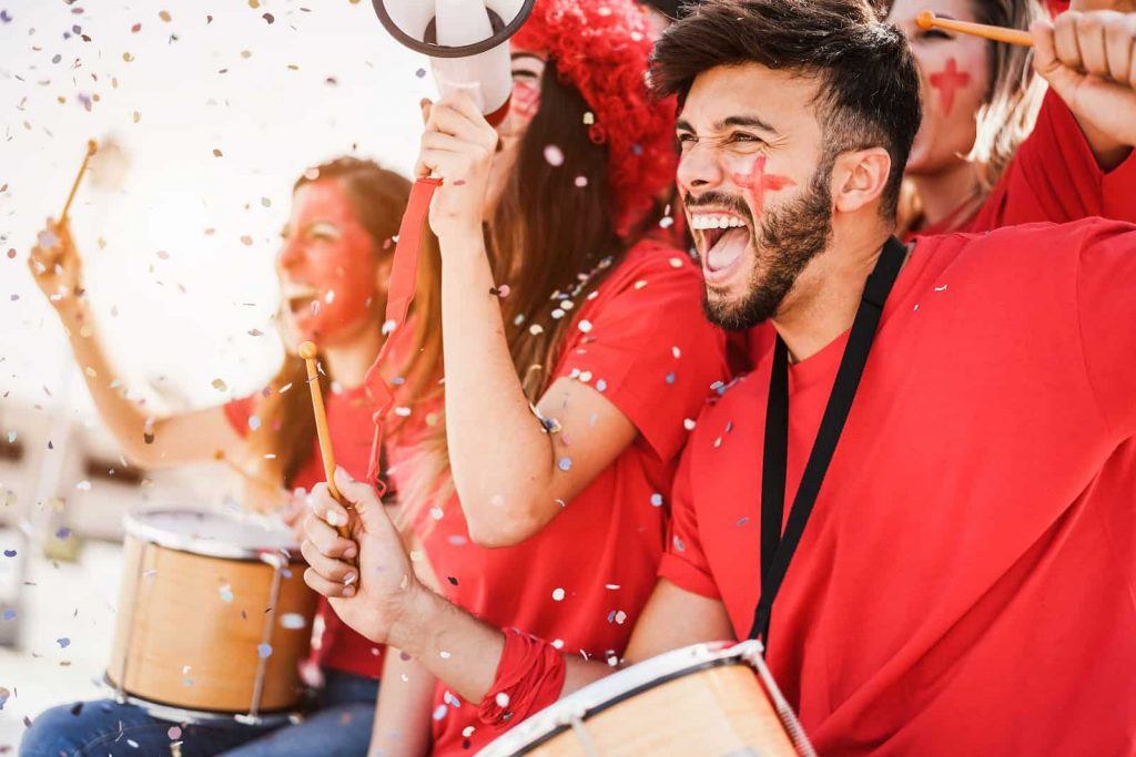 Sports fans all dressed in red cheering and drumming
