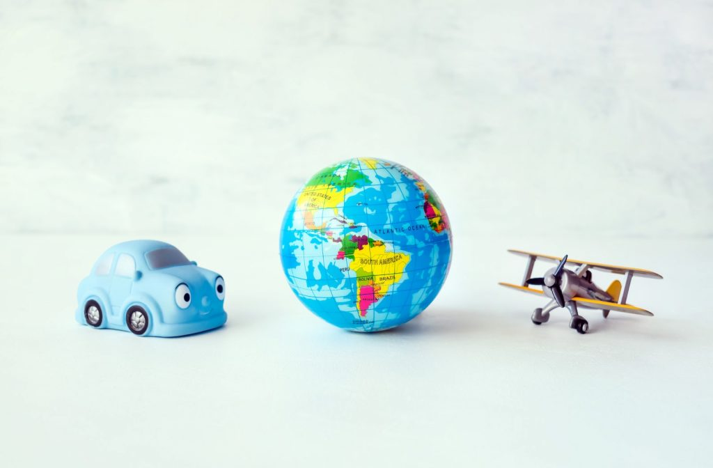 Toy blue car globe and toy model airplane representing the concept of ice breaker questions for virtual meetings.