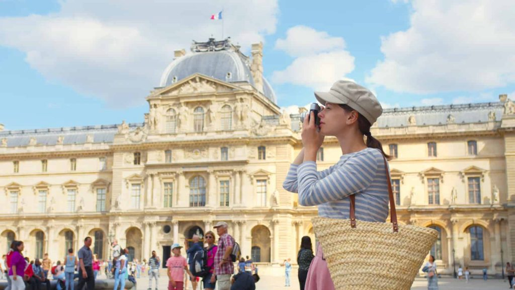 Women snapping a photo of a Paris landmark with a retro camera