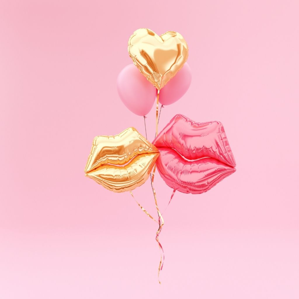 Two large helium balloons in the shape of lips with two smaller pink balloons and a gold heart balloon