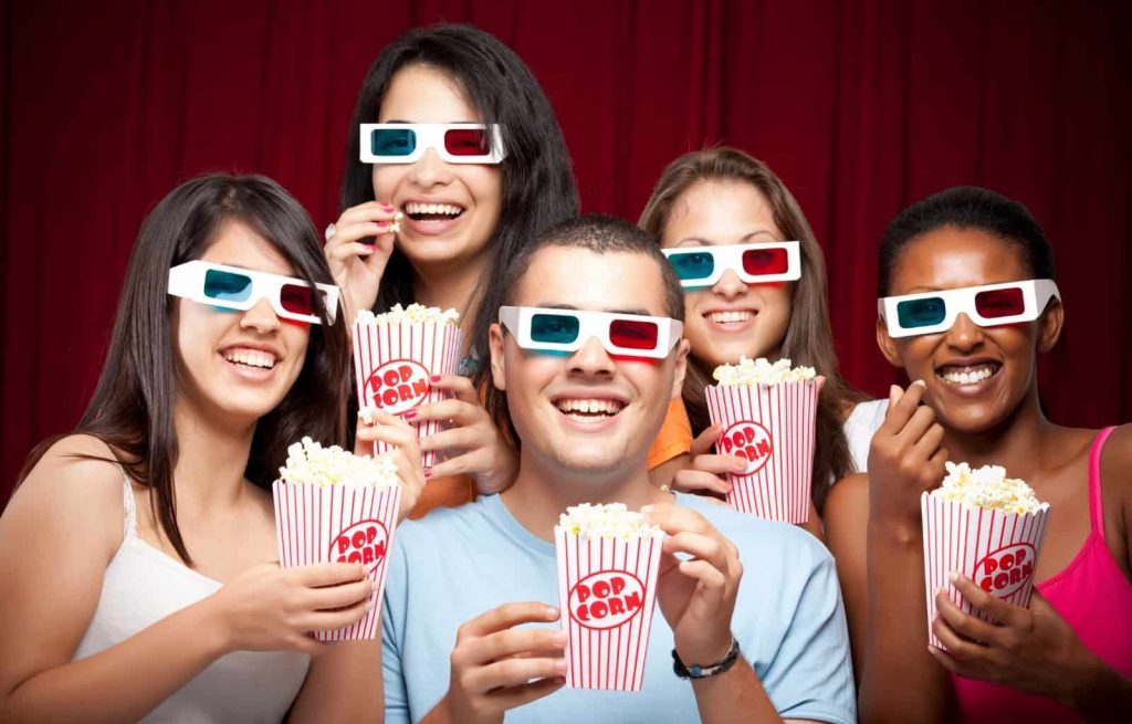 A group of people all wearing 3D movie glasses eating popcorn and smiling