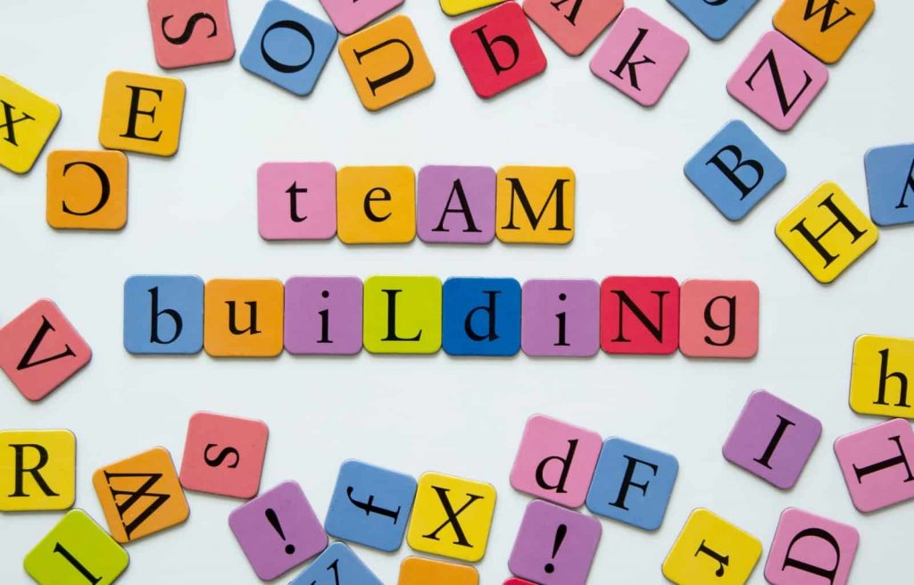 Colourful block letters scattered all around with the words team building in the center