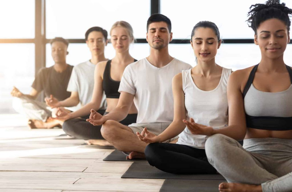 group of multicultural business people in the om position enjoying a meditation session together