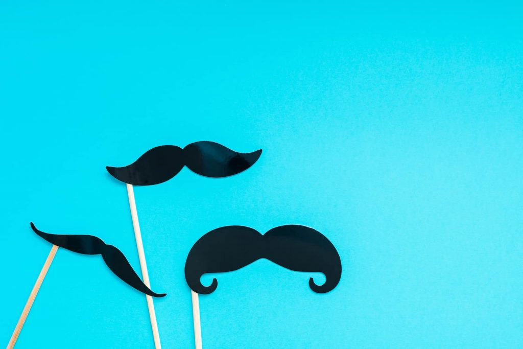 paper moustaches on blue background