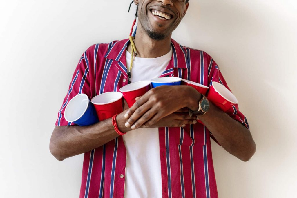 Young African American man holding red and blue plastic cups getting ready to play a virtual happy hour game
