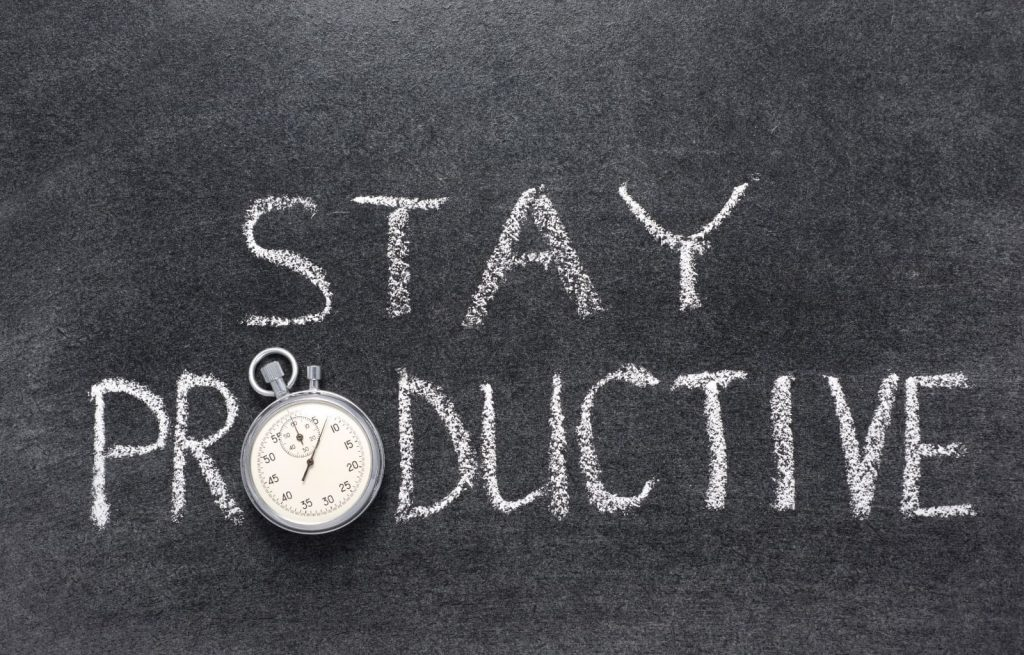 Stay productive written on a black chalkboard and a stop watch