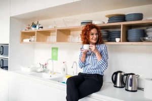 Business women sitting on top of counter in office kitchen