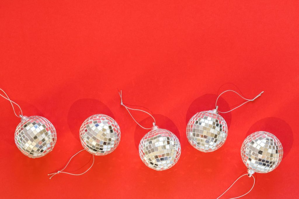 mirrored disco ball ornaments on a red background